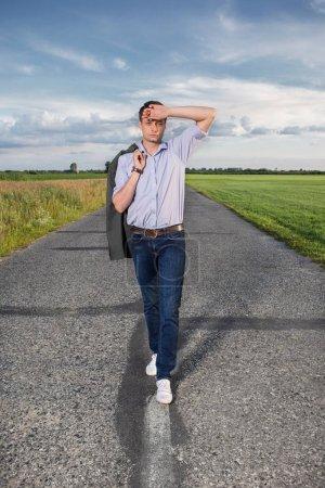 tired man walking alone on road