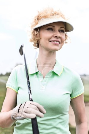 Thoughtful middle-aged woman on golf course