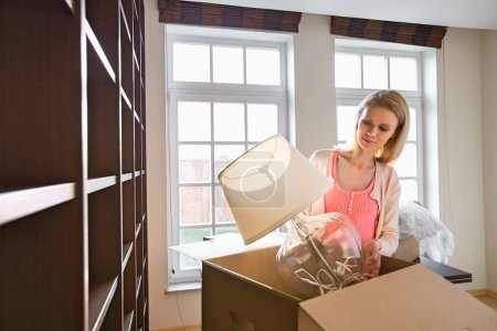 Photo for Woman removing lamp from cardboard box at new home - Royalty Free Image