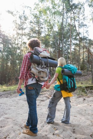 Couple with backpacks walking in forest