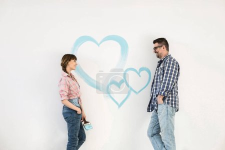 Couple with painted hearts on wall