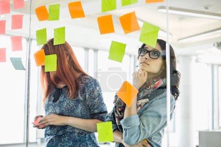 Creative businesswomen reading sticky notes