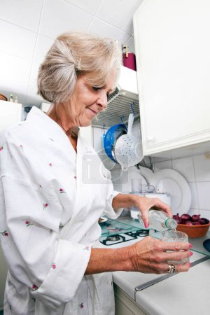 Senior woman pouring water in glass