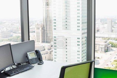 Desk by glass window in office