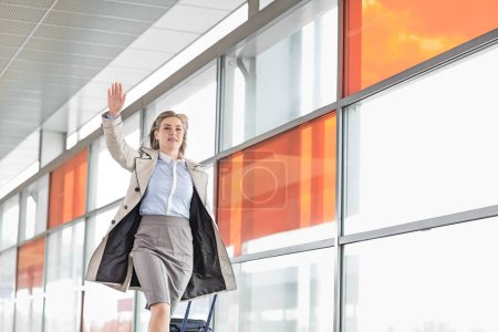 Businesswoman with luggage running