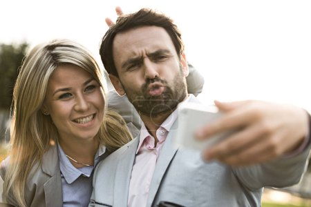 Playful business couple taking selfie
