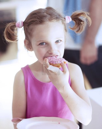 Photo for Young girl eating cake in kitchen - Royalty Free Image