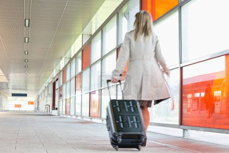Young businesswoman with luggage rushing
