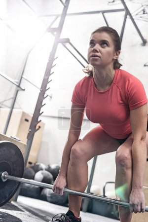 Confident woman lifting barbell