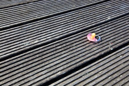 Photo for Dropped pacifier on wooden flooring - Royalty Free Image