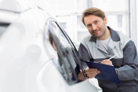 automobile mechanic holding clipboard