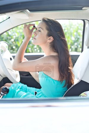 woman applying mascara in car