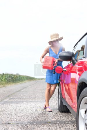 woman refueling car on country road