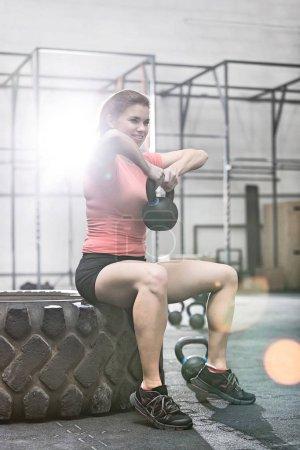 Smiling woman lifting kettlebell
