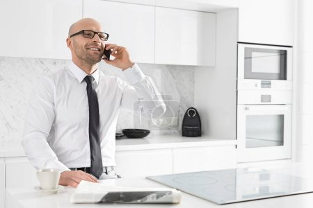 Businessman on call at kitchen
