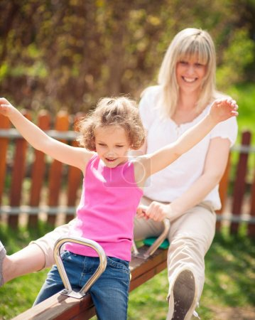 Mother and daughter ride seesaw