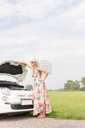 Photo for Full-length of tensed woman standing by broken down car on country road - Royalty Free Image