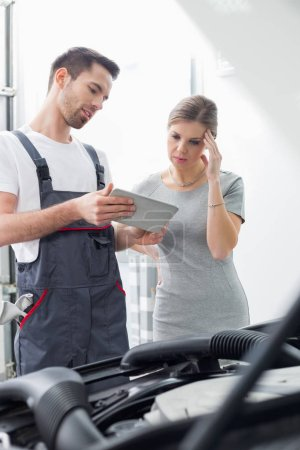 engineer showing digital tablet to customer
