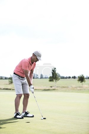 middle-aged man playing golf