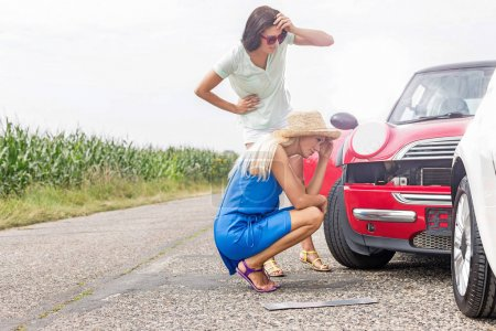 Tensed women looking at damaged cars