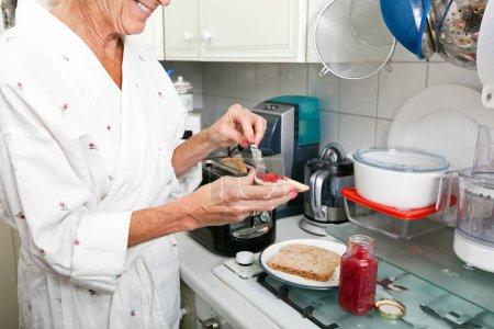 senior woman applying jam on toast