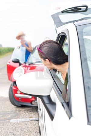 Woman looking at female crashing car