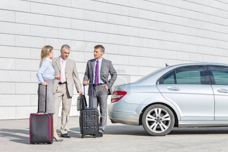 Businesspeople with luggage discussing