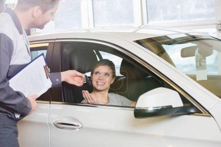 customer receiving car key from mechanic