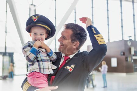 Photo for Portrait of mature pilot carrying cute little child in airport - Royalty Free Image