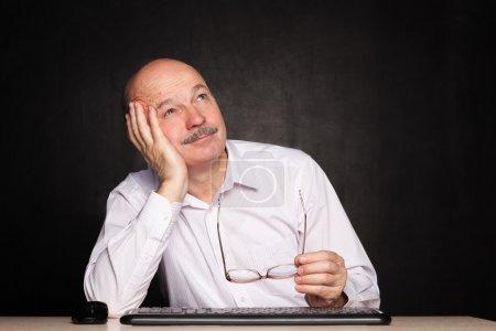 elderly man at work dreamily looks away during a break.