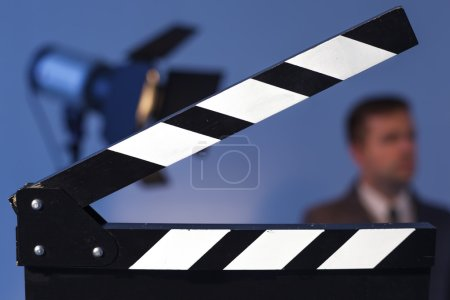 clapperboard and flashlight with TV presenter in a suit or model. Man waving at the camera