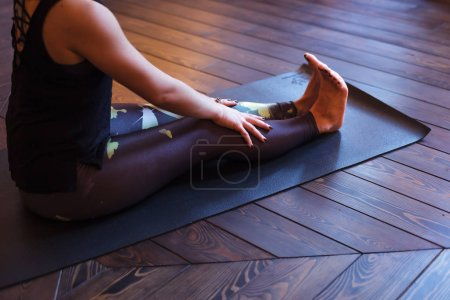 Photo for Girl sits on a mat with straight legs doing yoga - Royalty Free Image