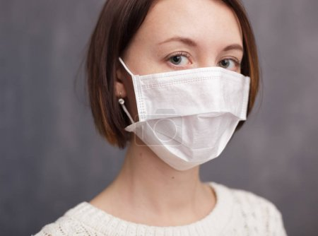 Photo for Girl in medical disposable mask looking at the camera. - Royalty Free Image