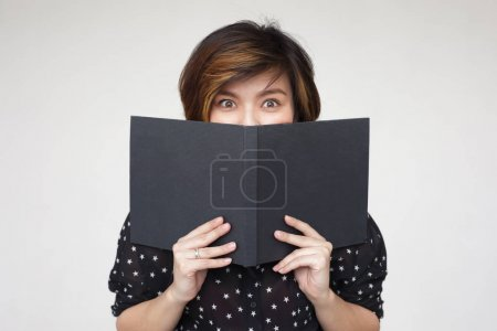 Asian girl covers her face with book