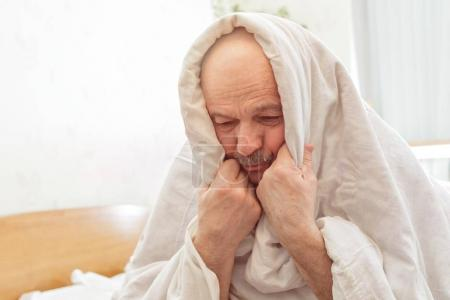 Hombre mayor triste sufre de insomnio .