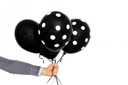 Photo pour Un homme caucasien tient à la main des ballons noirs. Présent pour le triste événement - image libre de droit