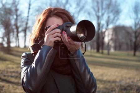 The girl holds a camera in her hands and takes a picture