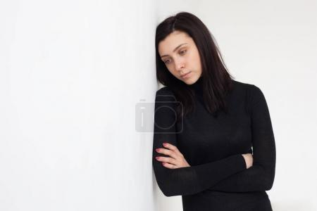 A beautiful girl in black clothes leaned her head against the wh