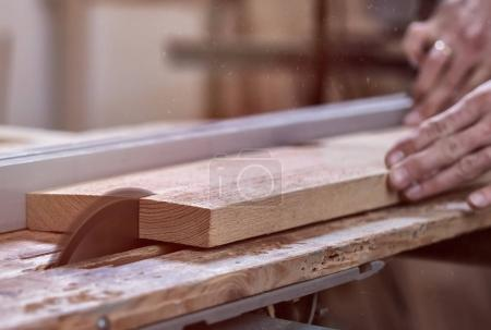 The joiner saws a piece of wood in 2 parts on with electric tool