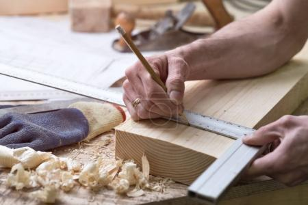 The carpenter makes marks with a pencil on a wooden strip.