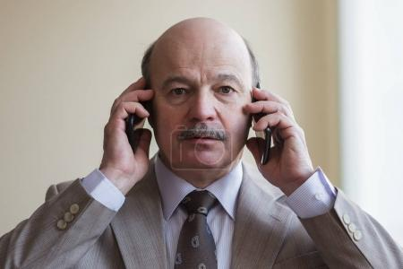 A busy businessman in a suit tries to talk on two phones simultaneously.
