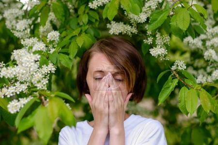 Una hermosa chica está junto a la cereza pájaro en flor y estornudar