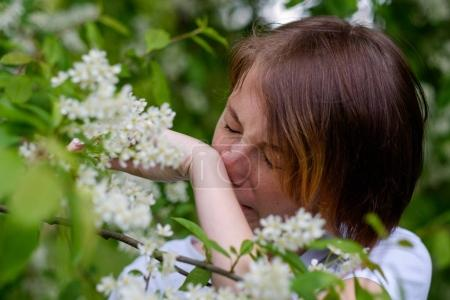 A beautiful girl stands by the blossoming bird cherry and sneeze