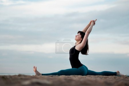 Girl practicing yoga in nature hanumanasana monkey pose.