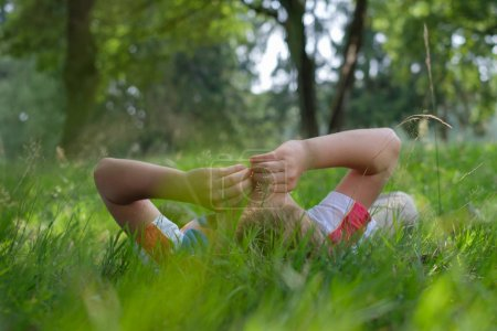 Boy lying on grass outdoors in summer park