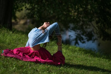 Beautiful young woman in red skirt practicing Yoga asana in nature