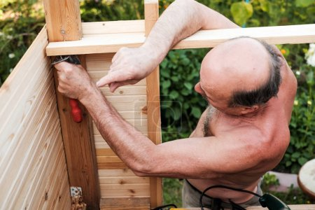 Mature man using tools building structure outside