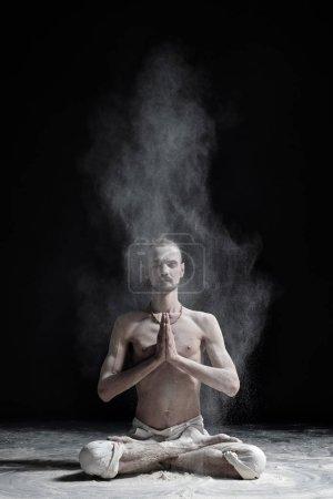 A yoga teacher sits in a sukhasana on a black background.