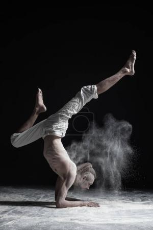 Flexible yoga man doing hand balance asana vrischikasana.