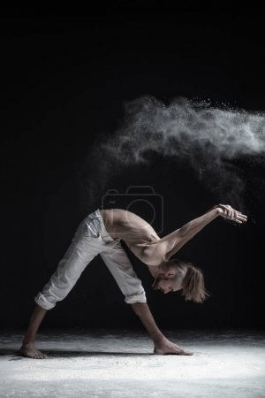 Young attractive yogi man practicing yoga, standing in Parivrtta Parsvatanasana exercise, working out